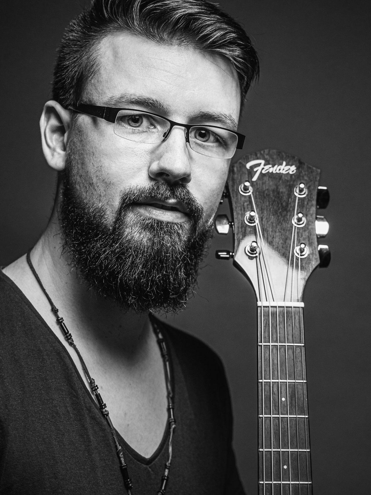 Junger man mit Bart und Gitarre